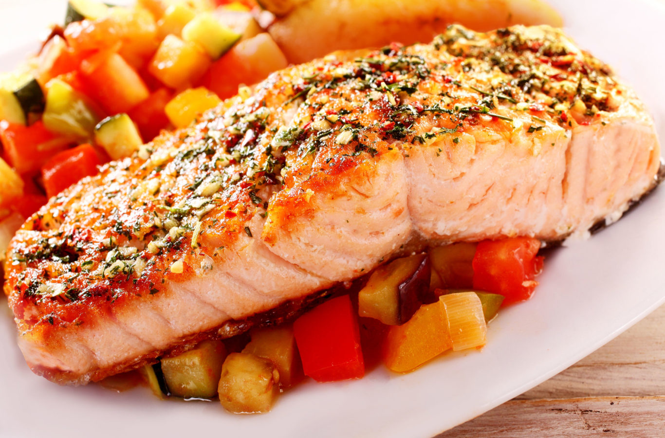 Close Up of Herb Roasted Fillet of Salmon Served on Bed of Fresh Chopped Salsa and Served on White Dish