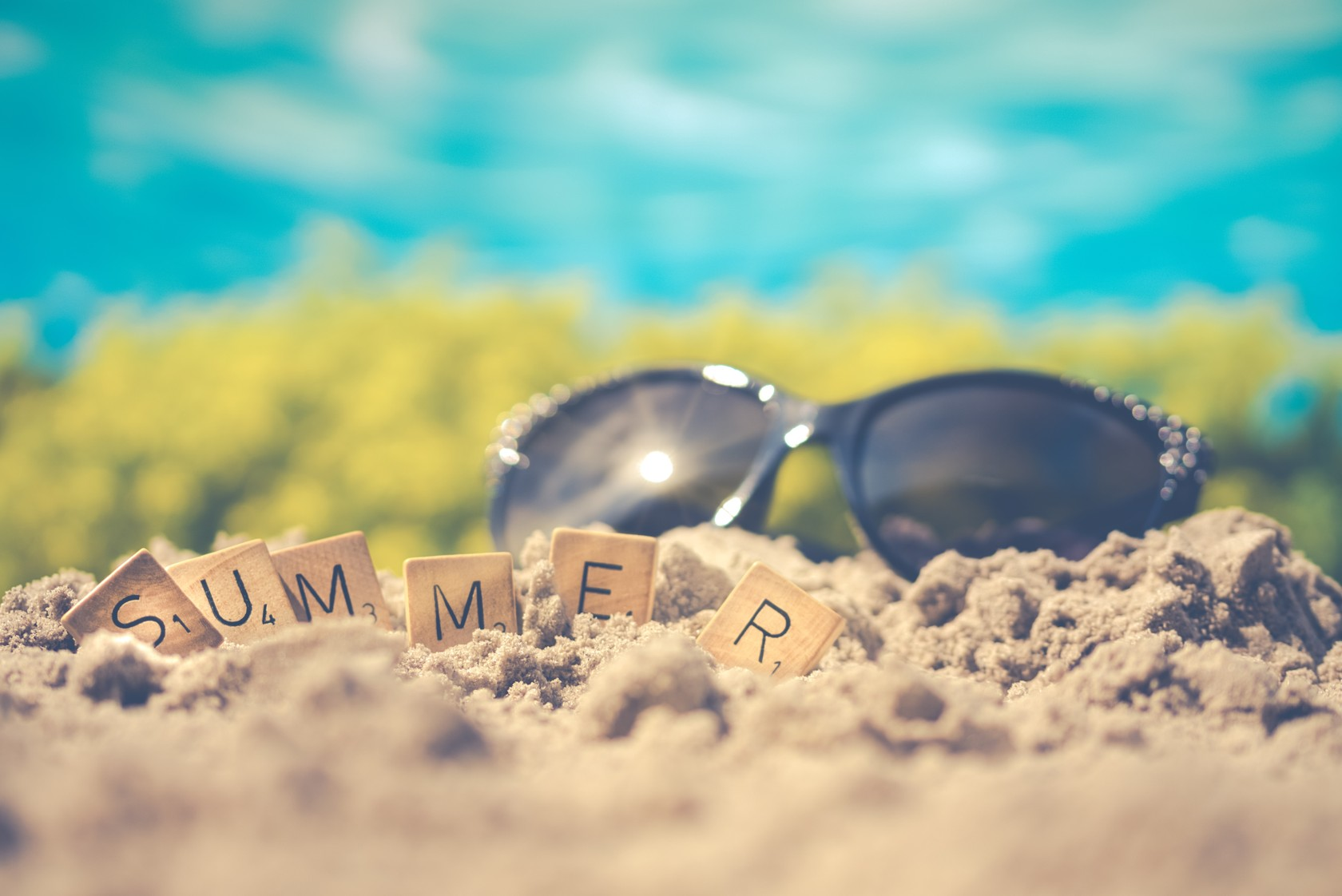 Sunglasses and summer letters on the beach
