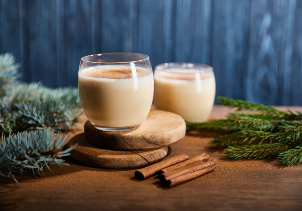 tasty eggnog cocktail on round wooden boards near spruce branches and cinnamon sticks on blue textured background