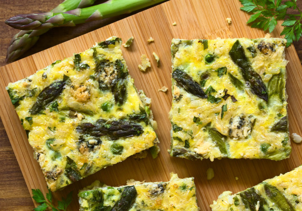Frittata made of eggs, green asparagus, pea, blue cheese, parsley and brown rice, photographed overhead on wooden board with natural light